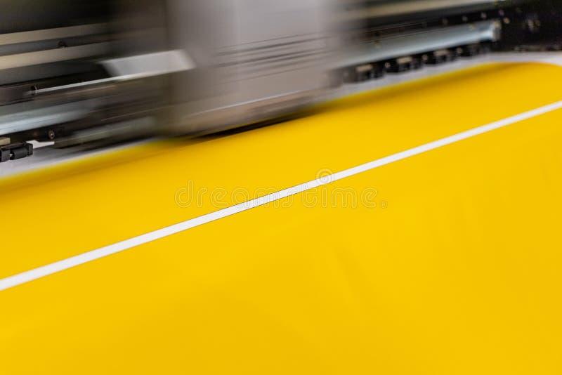 De grote professionele printer, die een grote schaal glanzend blad van geel document verwerken rolt voor kleurenbemonstering royalty-vrije stock afbeeldingen