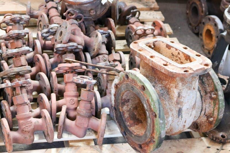 De grote roestige oude klep van de metaalpoort, pijpmontage, tegen de achtergrond van kleine kleppen, pijpleidingskleppen in de f royalty-vrije stock afbeelding