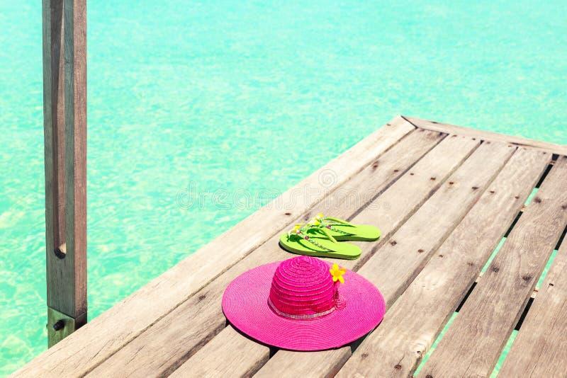 De grote roze zonhoed en de groene tik ploffen op het dek door het overzees royalty-vrije stock afbeeldingen