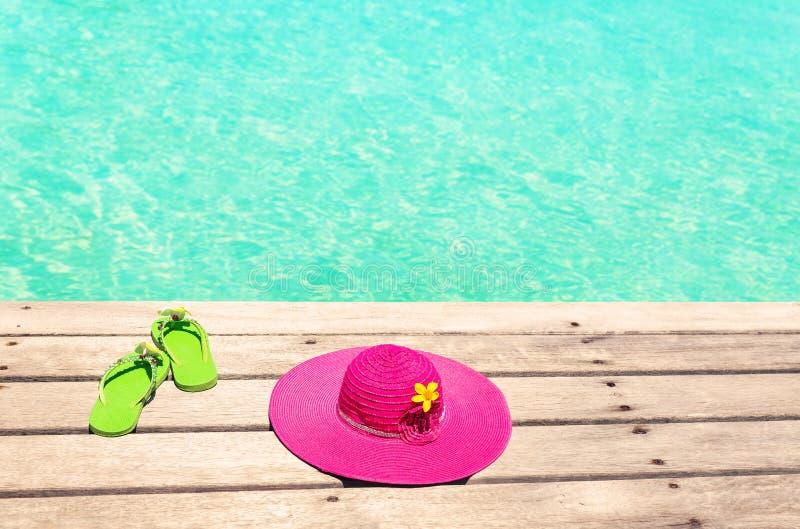 De grote roze zonhoed en de groene tik ploffen op het dek door het overzees royalty-vrije stock fotografie