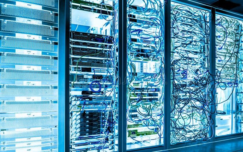 De grote ruimte van de gegevens donkere server met helder materiaal stock fotografie