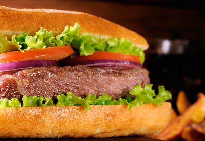 De grote sappige hamburger roosterde dicht omhoog stock foto