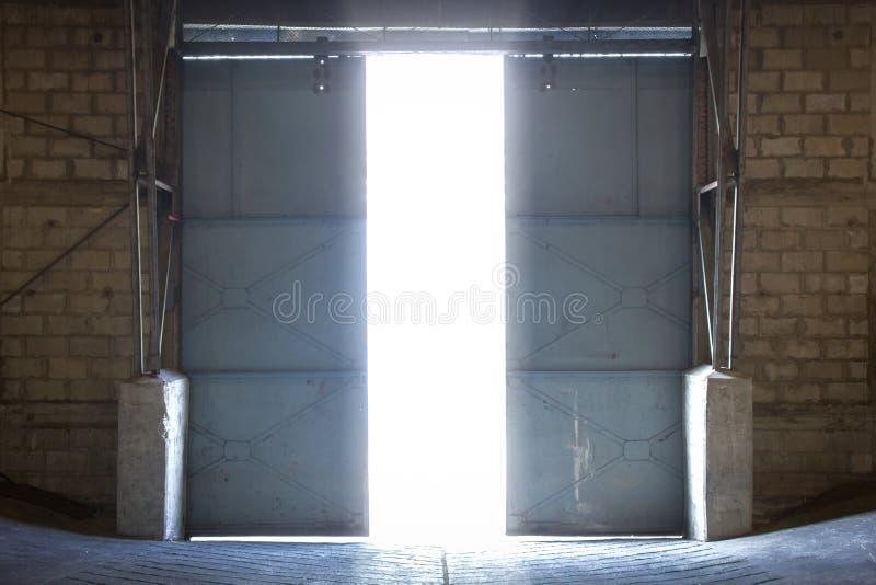 De grote staaldeur binnen een oud pakhuis opent in een extern licht royalty-vrije stock fotografie