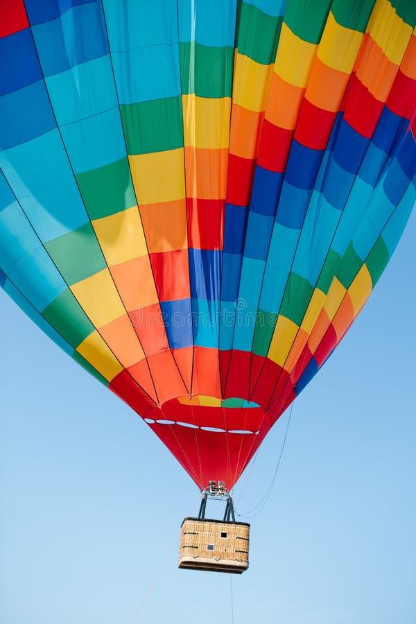De grote veelkleurige hete luchtballon stijgt in een blauwe duidelijke hemel royalty-vrije stock afbeelding