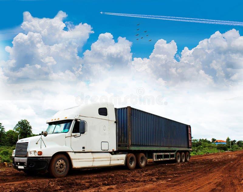 De grote vervoervrachtwagen met de modderlandweg, de mooie hemelwolk, onweer, onweersbuihemel betrekt stock foto's