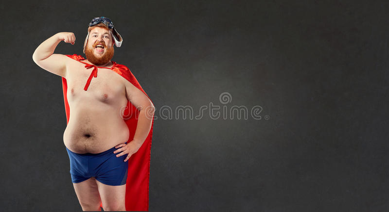 De grote vette naakte mens in een superherokostuum toont de spieren op hallo stock afbeelding