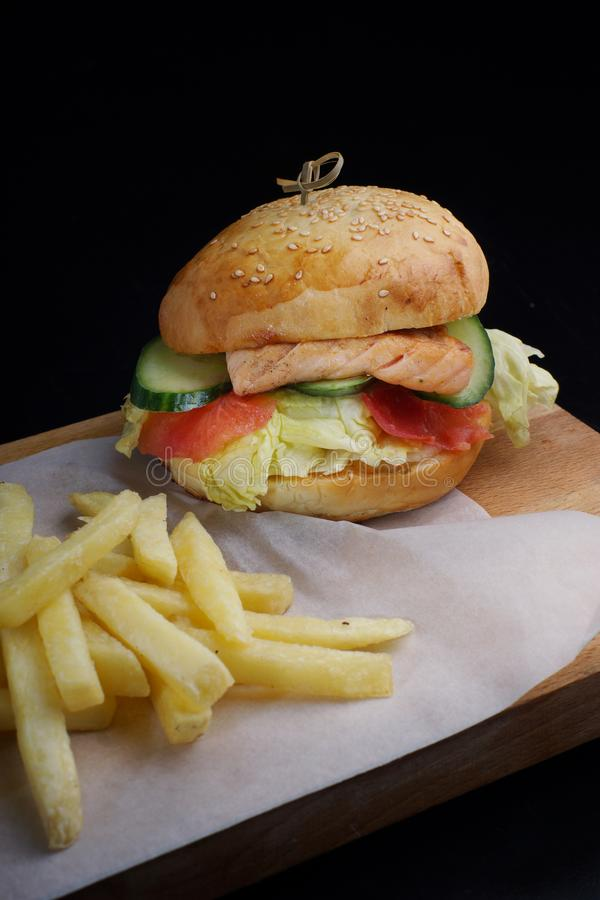 De grote vissenhamburger met forelfilet en salade diende op een raad met frieten stock afbeelding