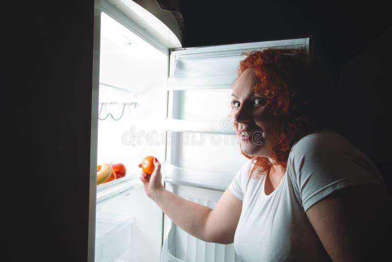 De grote vrouw eet fruit Rood haar vet meisje die binnenrefrigerat kijken royalty-vrije stock afbeeldingen