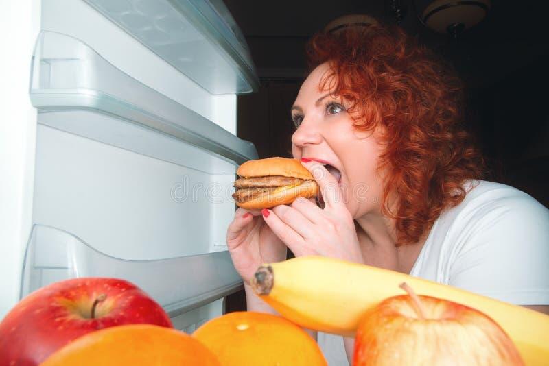 De grote vrouw eet snel voedsel Rood haar vet meisje die binnenrefrig kijken stock fotografie