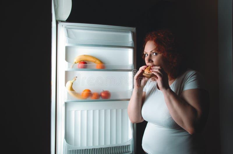 De grote vrouw eet snel voedsel Rood haar vet meisje die binnenrefrig kijken stock afbeelding