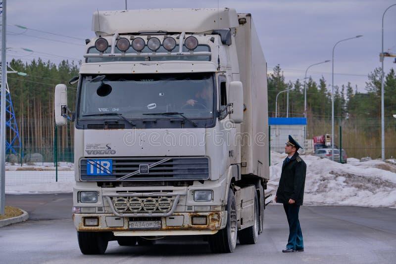 De grote wagen bij de douane post de commies benaderde de vrachtwagenchauffeur om de documenten te controleren stock fotografie