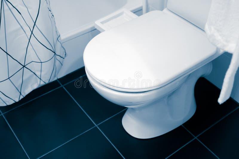 De grote witte en ceramische inrichting van de toiletzetel Douche, gordijn Witte badjas op een hanger stock foto's