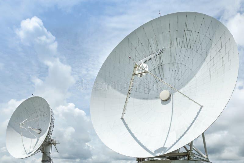 De grote grote witte satellietschotels verschijnen skyward op blauwe hemel royalty-vrije stock foto's