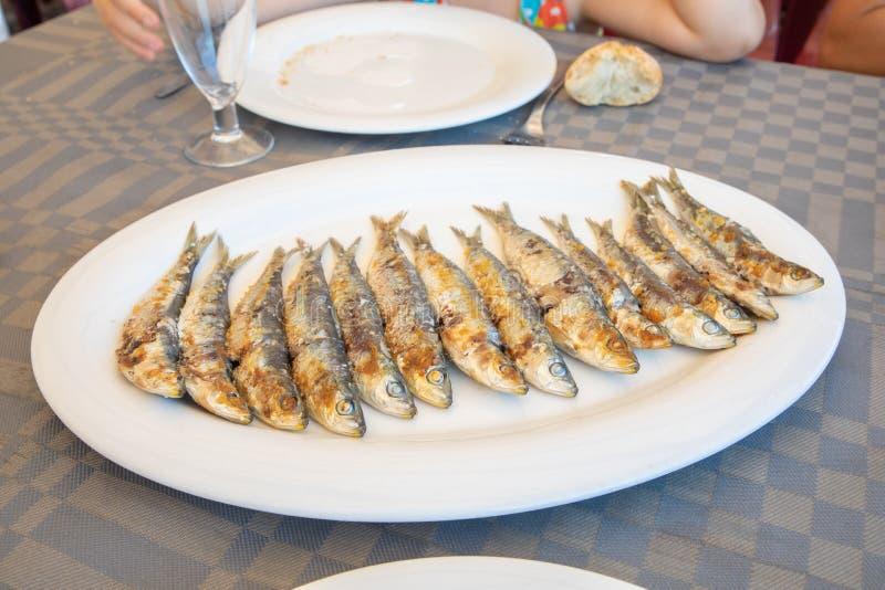 De grote witte schotel met een groep sardinesvissen kookte op een rij klaar te eten royalty-vrije stock afbeeldingen