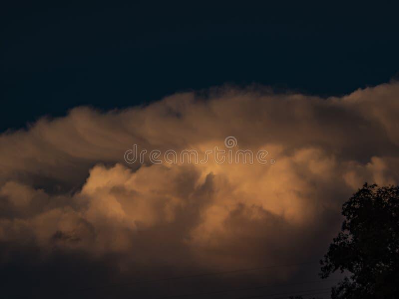 De grote wolken van de orangeand grijze cumulus wijzen op de kleuren van de zonsondergang royalty-vrije stock fotografie