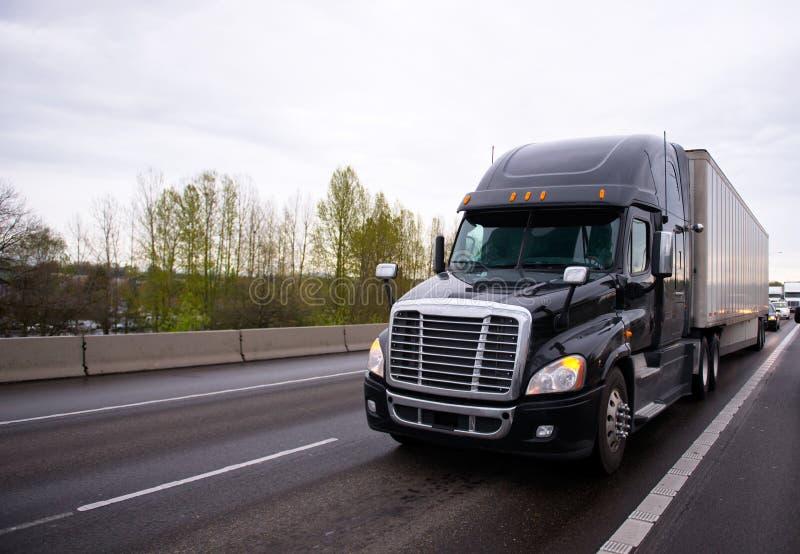 De grote zwarte moderne semi aanhangwagen van de vrachtwageninstallatie in verkeer op weg royalty-vrije stock afbeelding