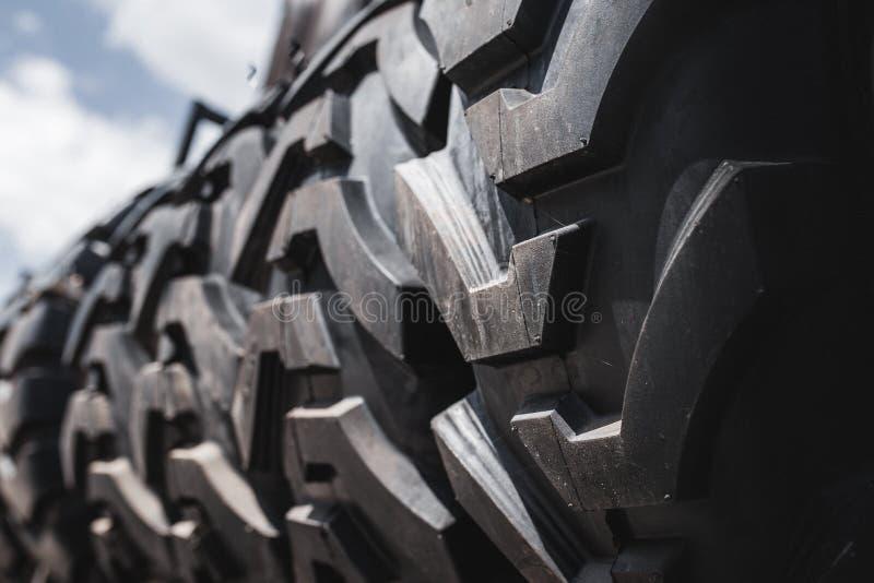 De grote zwarte reusachtige grote vrachtwagen, tractor of bulldozerladerbanden rijden close-up op tribune, winkel verkopende band royalty-vrije stock afbeeldingen
