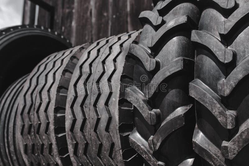 De grote zwarte reusachtige grote vrachtwagen, tractor of bulldozerladerbanden rijden close-up op tribune, winkel verkopende band stock foto's