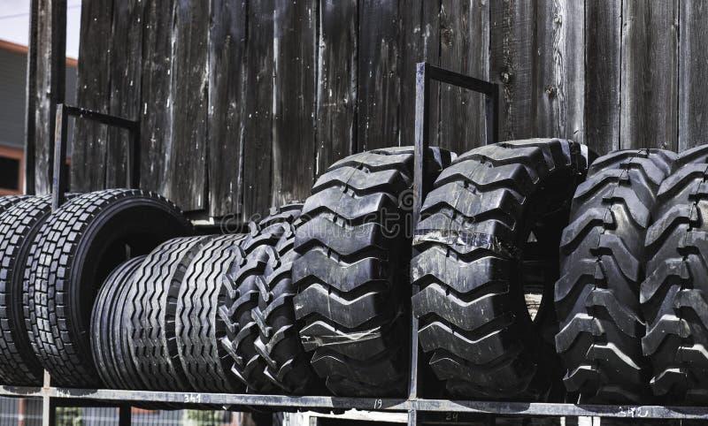 De grote zwarte reusachtige grote vrachtwagen, tractor of bulldozerladerbanden rijden close-up op tribune, winkel verkopende band royalty-vrije stock afbeelding