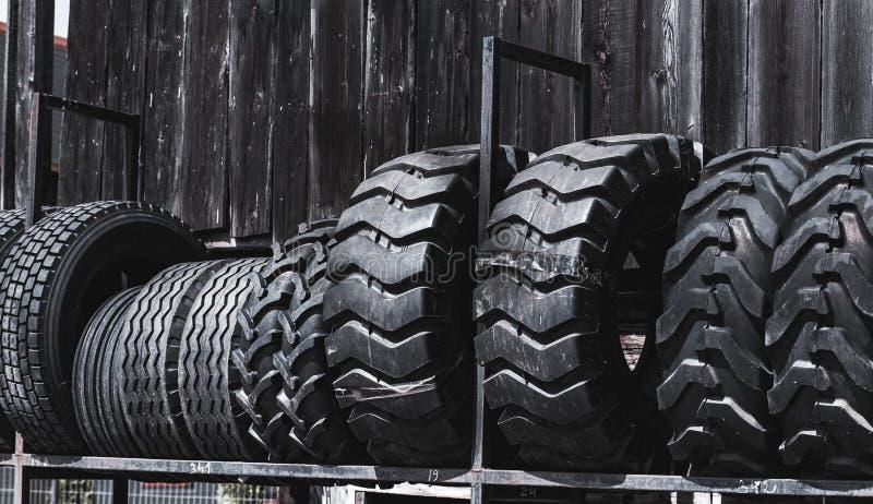 De grote zwarte reusachtige grote vrachtwagen, tractor of bulldozerladerbanden rijden close-up op tribune, winkel verkopende band royalty-vrije stock fotografie