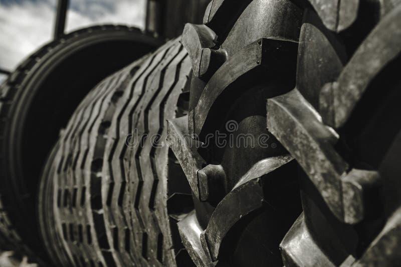 De grote zwarte reusachtige grote vrachtwagen, tractor of bulldozerladerbanden rijden close-up op tribune, winkel verkopende band royalty-vrije stock foto's