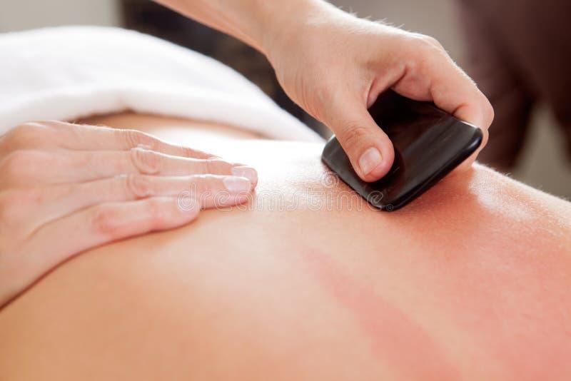 De Gua-Sha de la acupuntura del tratamiento parte posterior encendido fotos de archivo