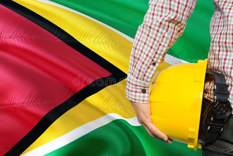 De Guinese Ingenieur houdt gele veiligheidshelm met golvende de vlagachtergrond van Guyana Bouw en de bouwconcept stock foto's