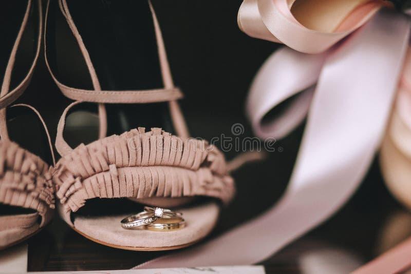 De guld- cirklarna för bröllop med diamanter ligger på rosa brudskor för sammet med satängband Närbild royaltyfri fotografi