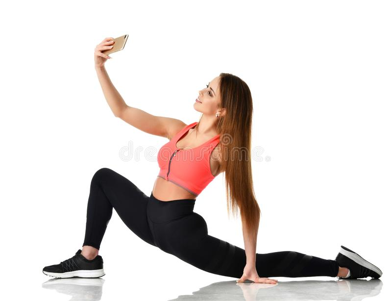 De gymnastiek die van de sportvrouw uitrekkende fitness oefeningstraining doen en maakt selfie op haar mobiele cellphone stock fotografie