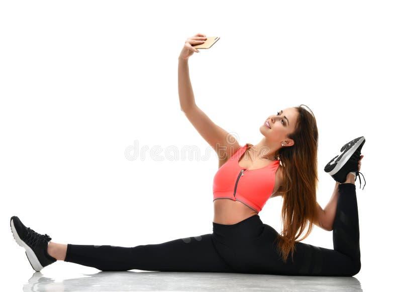 De gymnastiek die van de sportvrouw uitrekkende fitness oefeningstraining doen en maakt selfie op haar mobiele cellphone stock foto's