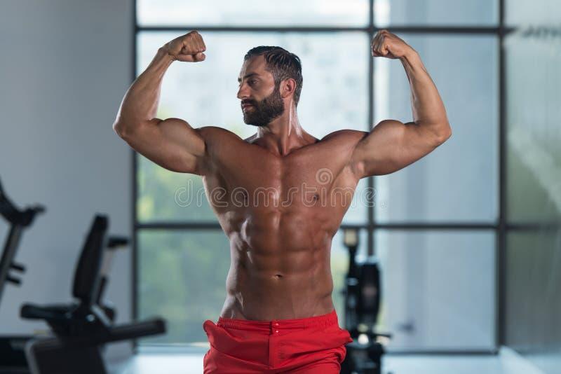 De Gymnastiek van Front Double Biceps Pose In van de bodybuilderverbuiging royalty-vrije stock afbeeldingen