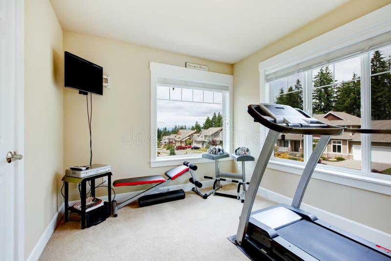 De gymnastiek van het huis met apparatuur, gewichten en TV. stock fotografie