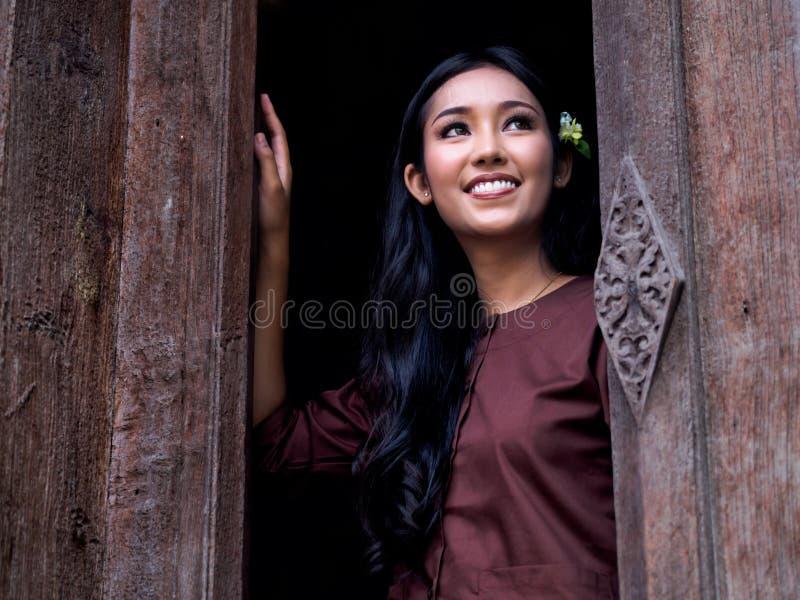 De härliga flickaleendena i den asiatiska klänningen forntida Thailand fotografering för bildbyråer