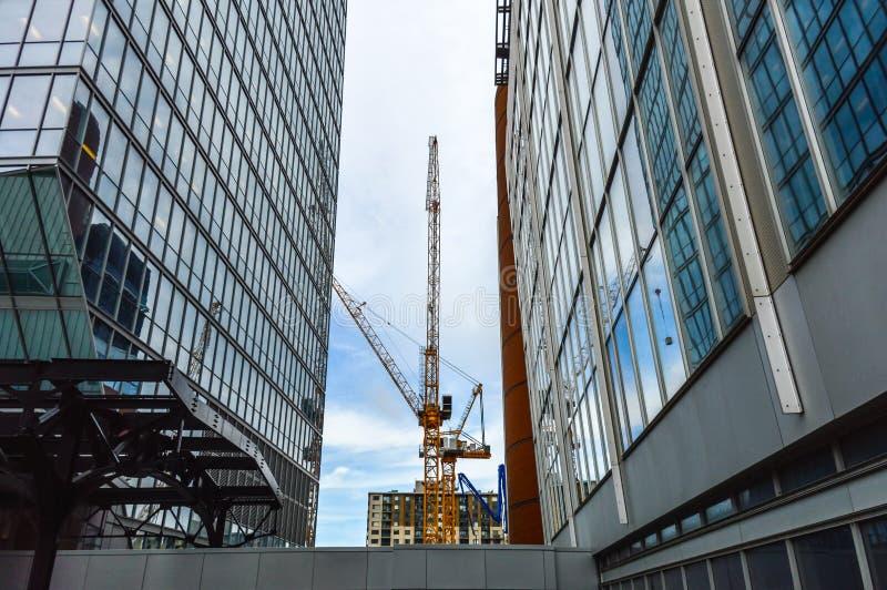 De högväxta affärsskyskraporna och konstruktionskranen I royaltyfri bild