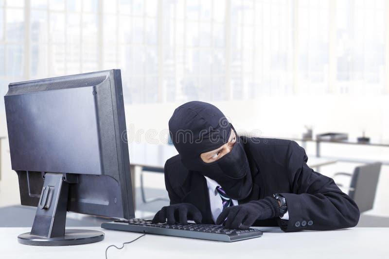 De hakker steelt gegevens in het bureau royalty-vrije stock foto's