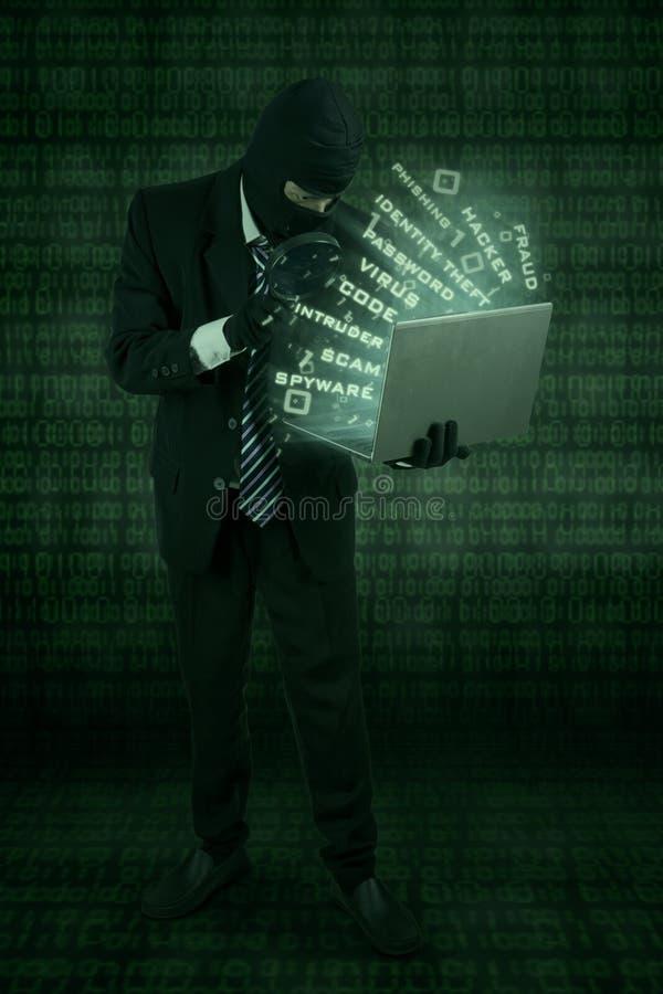 De hakker steelt gegevens met laptop stock afbeelding