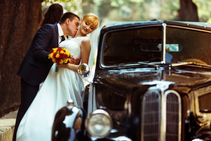 De hals die van de bruid van Fiancekussen zich achter een zwarte retro auto bevinden royalty-vrije stock afbeeldingen