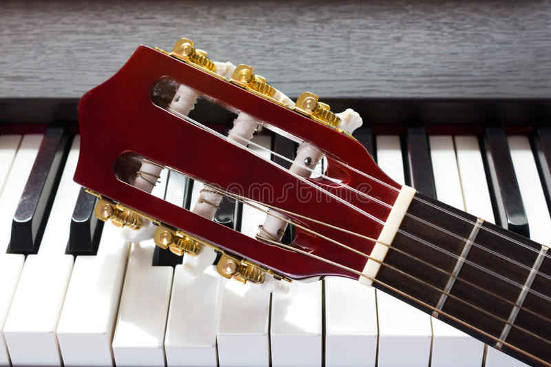 De hals van de gitaar op pianosleutels stock foto