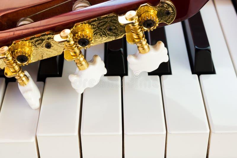De hals van de gitaar op pianosleutels stock afbeelding