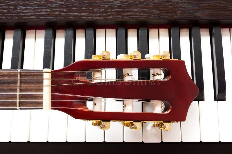 De hals van de gitaar op pianosleutels stock foto's