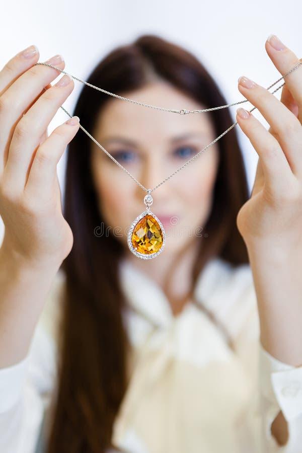 De halsband van de vrouwenholding met gele saffier stock afbeelding