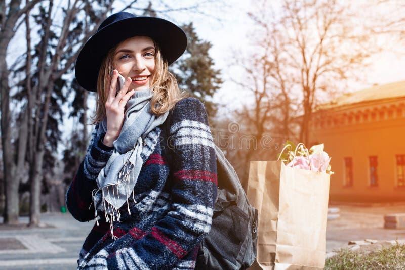 De halve gelukkige jonge vrouw van het lengteportret kleedde zich in modieuze kleren die op mobiele telefoon met binnen vriend op stock fotografie