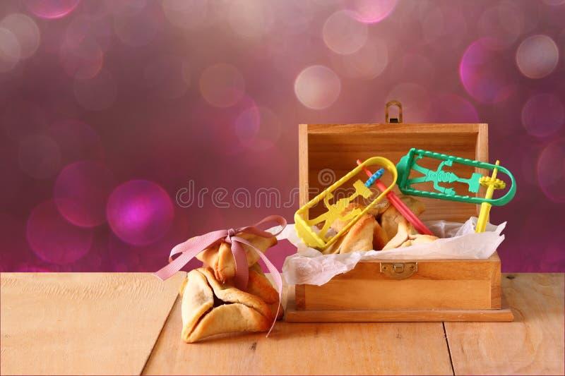 De Hamantaschenkoekjes of hamans de oren en het masker voor Purim-viering (Joodse vakantie) en schitteren achtergrond stock afbeelding