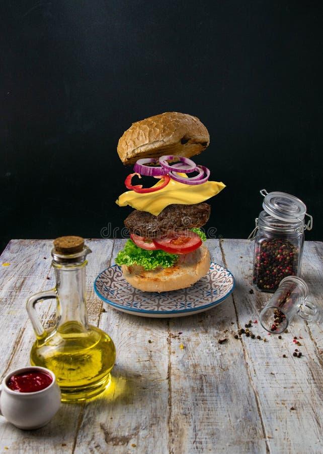 De hamburger` s verschijning is verschillend Het indienen op een witte houten achtergrond stock afbeelding