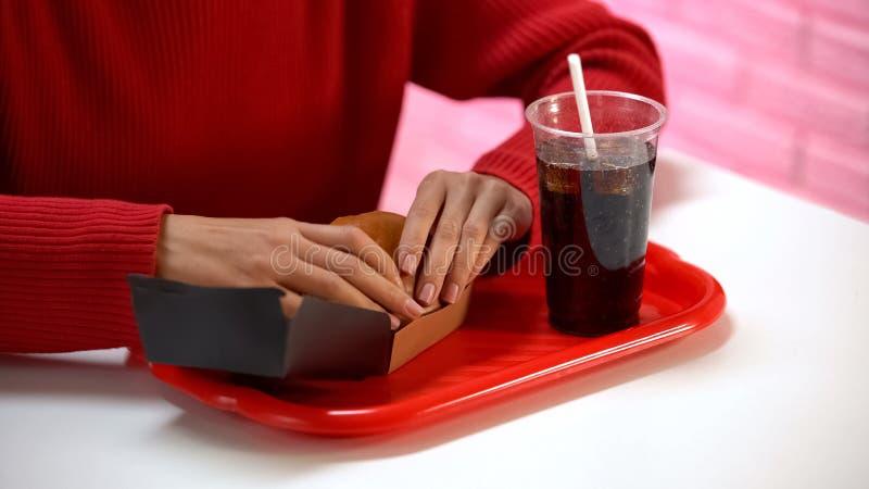 De hamburger van de dameholding met frisdrank, ongezonde kostvoeding, vette maaltijd, calorie?n stock afbeelding