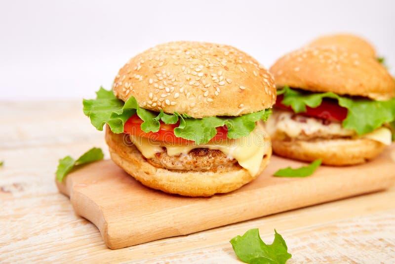 De hamburger van het ambachtrundvlees op houten lijst aangaande lichte achtergrond stock fotografie