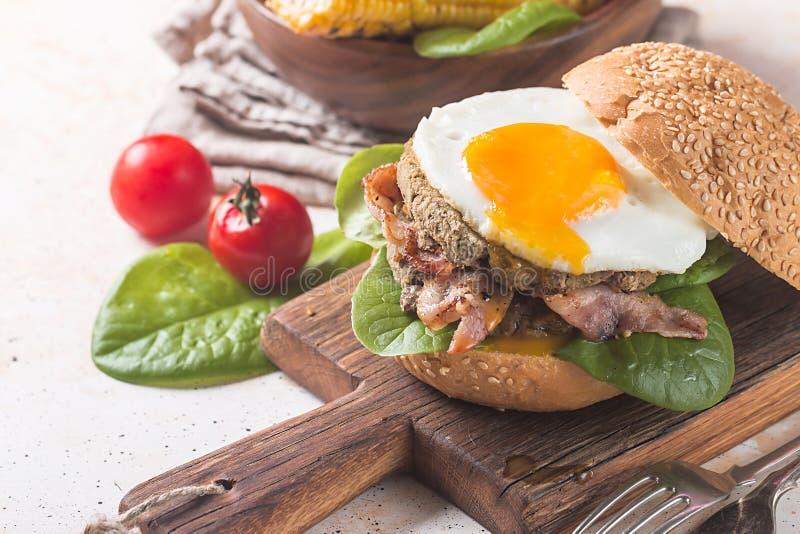 De Hamburger van het Homemmadebacon met gebraden Ei stock afbeelding