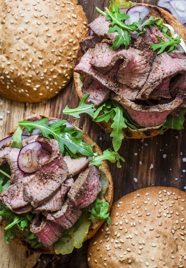 De hamburger van het rundvleeslapje vlees met groenten in het zuur, de saus van Mayo, arugula en rode ui op een rustieke houten r royalty-vrije stock afbeeldingen