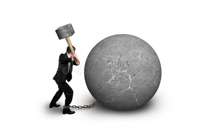 De hamer die van de zakenmanholding gebarsten concrete bal raken isoleert royalty-vrije stock afbeeldingen