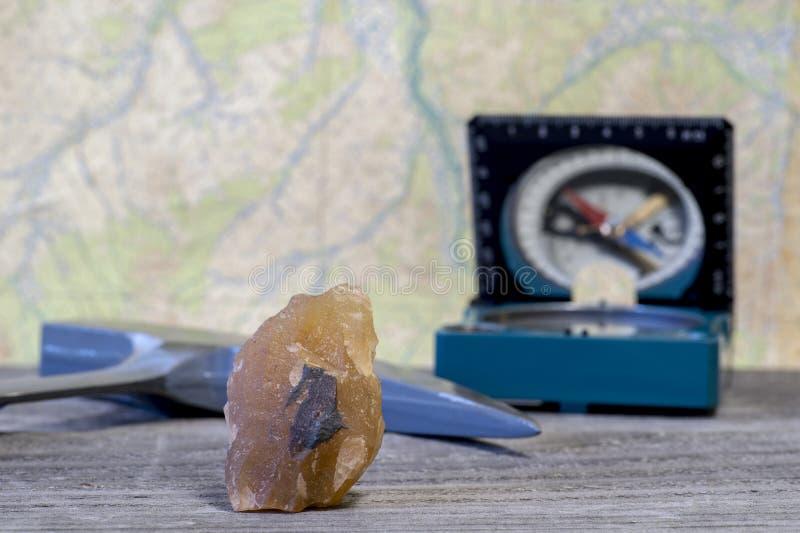 De hamer van een geoloog, een kompas en een mineraal die met ijzererts is doorweven, zijn op een houten tafel gelegd royalty-vrije stock foto